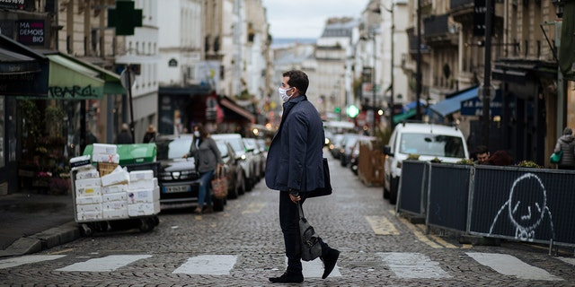 A man wearing a mask walks in the Montmartre district of Paris, Sunday, Oct.25, 2020. (AP Photo/Lewis Joly)