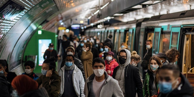 Commuters wearing face masks walk on the platform, of a Paris subway, Sunday Oct.25, 2020. (AP Photo/Lewis Joly)