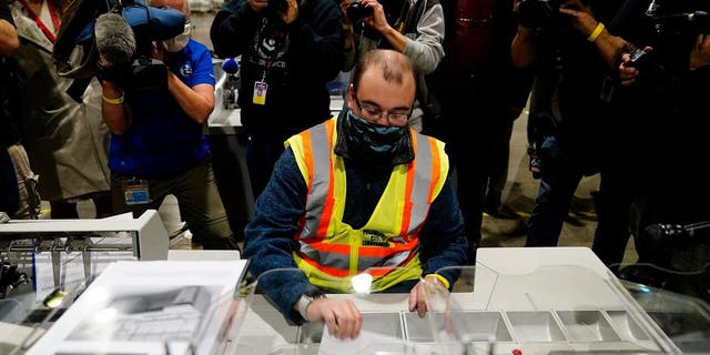 John Hansberry, with the Philadelphia City Commissioners office, demonstrates an extraction machine at the city's mail-in ballot sorting and counting center in preparation for the 2020 General Election in the United States, Lunedi, Ott. 26, 2020, a Philadelphia. (AP Photo/Matt Slocum)
