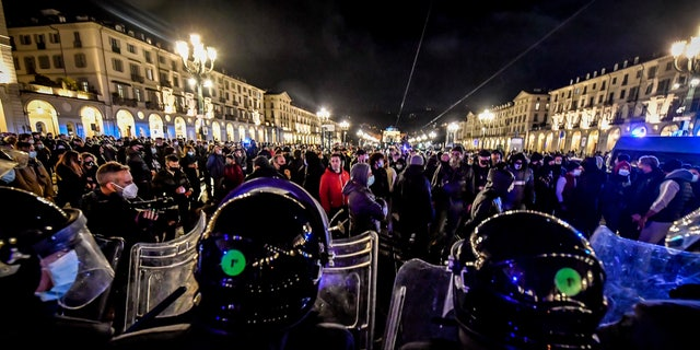 Police face people protesting the government restriction measures to curb the spread of COVID-19 in Turin, Italy, Maandag, Okt.. 26, 2020. (Claudio Furlan/LaPresse via AP)