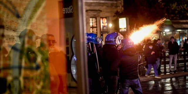 Police fire tear gas as clashes broke out during a protest against the government restriction measures to curb the spread of COVID-19 in Turin, Italy, Maandag, Okt.. 26, 2020. (Claudio Furlan/LaPresse via AP)
