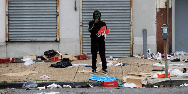 A man holds merchandise outside of a damaged store after protests, Tuesday, Oct. 27, 2020, in Philadelphia over the death of Walter Wallace, a Black man who was killed by police in Philadelphia. (AP Photo/Michael Perez)