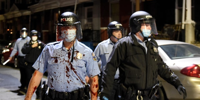 A Philadelphia police officer is covered with an unidentified red substance during a confrontation with protesters, Tuesday, Oct. 27, 2020, in Philadelphia. (AP Photo/Michael Perez)