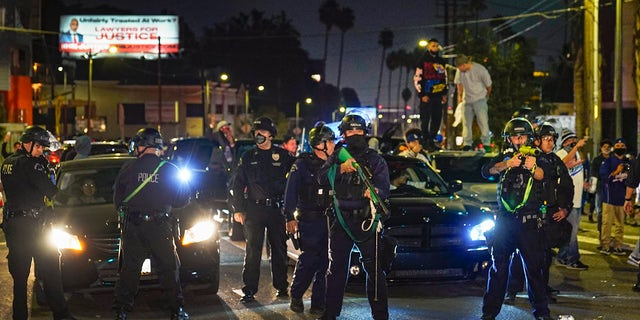 Members of the Los Angeles Police order fans to disperse on Sunset Boulevard after watching the broadcast of Game 6 of the baseball World Series in Los Angeles on Tuesday, Oct. 27, 2020. The Los Angeles Dodgers defeated the Tampa Bay Rays 3-1 and won the World Series. (AP Photo/Damian Dovarganes)