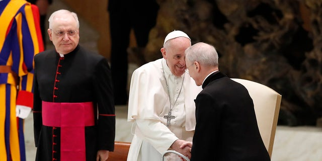 Pope Francis shakes hands with Monsignor Luis Maria Rodrigo Ewart as he arrives in the Paul VI Hall at the Vatican for his weekly general audience, Wednesday, Oct. 28, 2020. (AP Photo/Alessandra Tarantino)