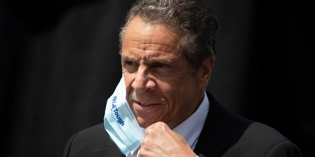 New York Gov. Andrew Cuomo removes a mask as he holds a news conference in Tarrytown, N.Y. (AP Photo/Mark Lennihan, File)
