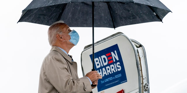 Democratic presidential candidate former Vice President Joe Biden, closes his umbrella as he boards his campaign plane at New Castle Airport in New Castle, 的。, 星期四, 十月. 29, 2020, to travel to Florida for drive-in rallies. (美联社照片/安德鲁·哈尼克)