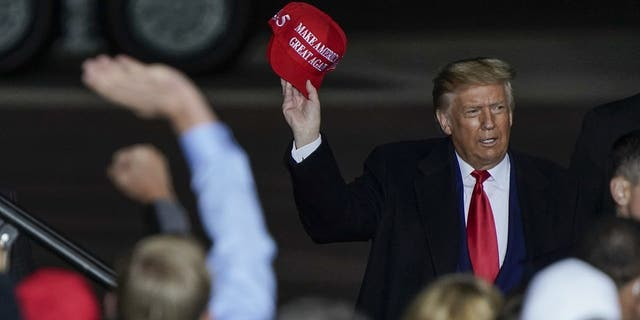 FILE - In this Sept. 17, 2020 file photo President Donald Trump throws a hat to the crowd after speaking at a campaign rally at the Central Wisconsin Airport in Mosinee, Wis. (AP Photo/Morry Gash, File)