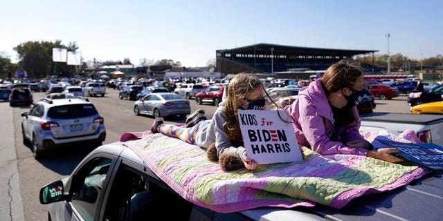 Children lie on the roof of a vehicle during a campaign rally for Democratic presidential candidate former Vice President Joe Biden at the Iowa State Fairgrounds in Des Moines, Iowa, Friday, Oct. 30, 2020. (AP Photo/Andrew Harnik)