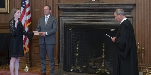 Chief Justice John G. Roberts, Jr., administers the Judicial Oath to Judge Amy Coney Barrett in the East Conference Room, Supreme Court Building. Judge Barrett's husband, Jesse M. Barrett, holds the Bible. (Credit: Fred Schilling, Collection of the Supreme Court of the United States)
