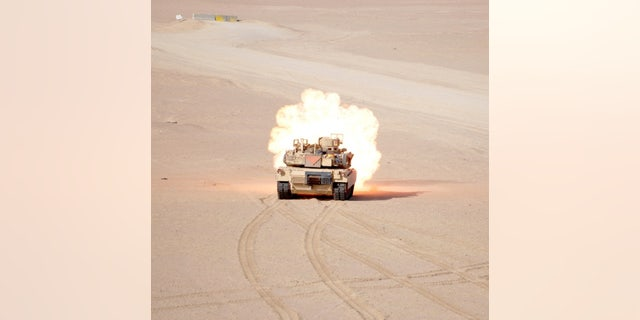 An M1A2 Abrams tanks assigned to 1st Battalion, 66th Armor Regiment, 3rd Armored Brigade Combat Team, 4th Infantry Division, fires a 120mm Sabot tank round at a target during Gunnery Live Fire Qualifications at the Udairi Range Complex, Kuwait, April 26, 2015 - lêerfoto.