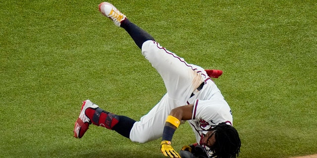 Atlanta Braves' Ronald Acuna Jr. falls at first base during the sixth inning in Game 4 of a baseball National League Championship Series against the Los Angeles Dodgers Thursday, Oct. 15, 2020, in Arlington, Texas. (AP Photo/Sue Ogrocki)