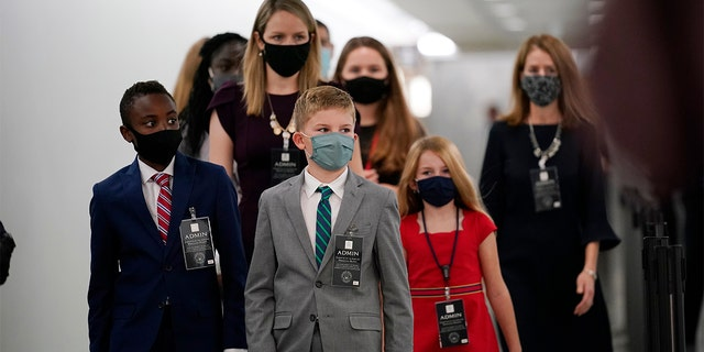 The children of Supreme Court nominee Amy Coney Barrett arrive on Capitol Hill before she will begin her confirmation hearing before the Senate Judiciary Committee, Monday, Oct. 12, 2020 on Capitol Hill in Washington. (AP Photo/J. Scott Applewhite)