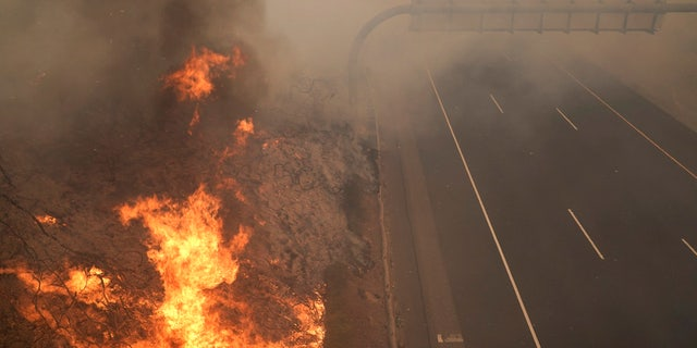 The Silverado Fire burns along the 241 State Highway Monday, Oct. 26, 2020, in Irvine, Calif.