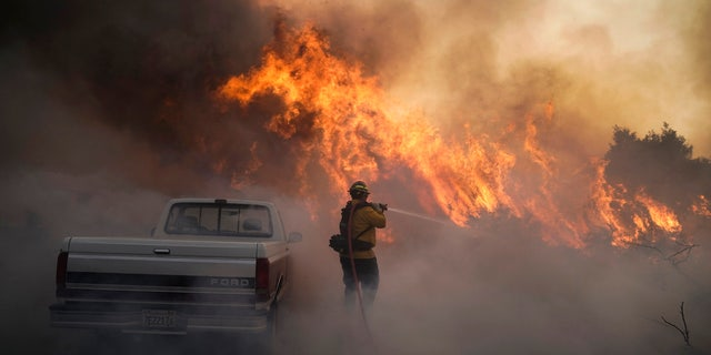 Firefighter Raymond Vasquez battles the Silverado Fire Monday, Oct. 26, 2020, in Irvine, Calif.