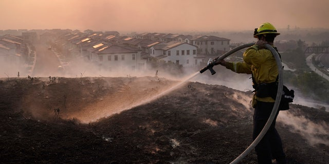Firefighter Tylor Gilbert puts out hotspots while battling the Silverado Fire, Monday, Oct. 26, 2020, in Irvine, Calif.