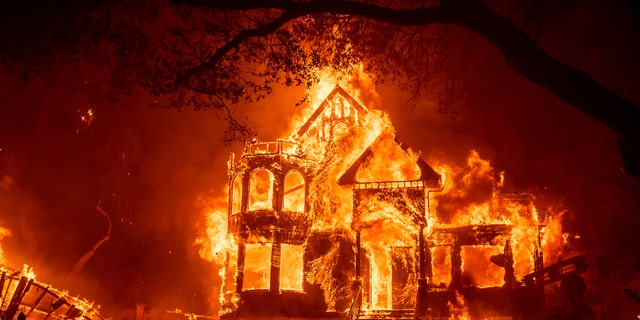 Flames from the Glass Fire consume the Black Rock Inn, late Sunday, Sept. 27, 2020, in St. Helena, Calif.