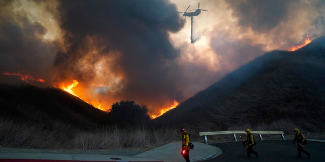 A helicopter drops water as firefighters walk with drip torches to set a backfire against the Blue Ridge Fire on Tuesday, Oct. 27, 2020, in Chino Hills, Calif.