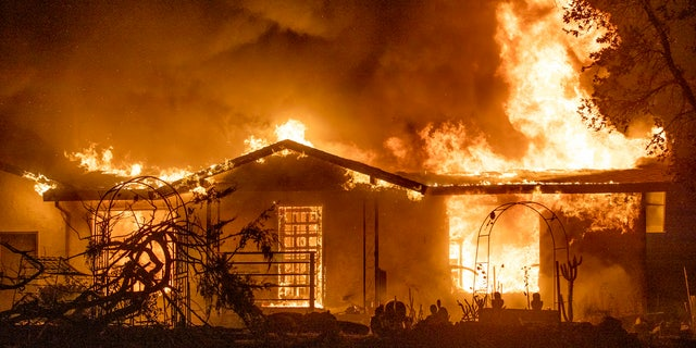In this Sept. 27, 2020, file photo, a house burns on Platina Road at the Zogg Fire near Ono, Calif.