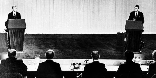 U.S. President Jimmy Carter, left, and Republican presidential candidate Ronald Reagan face their panelists during their televised debate at the Cleveland Convention Center in Cleveland, Ohio, on Oct. 28, 1980. (AP Photo)
