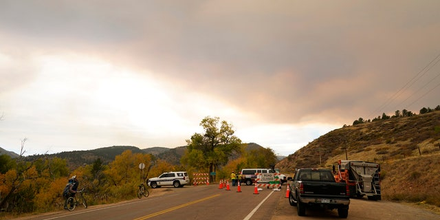 A funnel of smoke builds over a roadblock into a housing area along Highway 7 as several wildfires burn in the state Wednesday, Oct. 21, 2020, in Lyons, Colo.