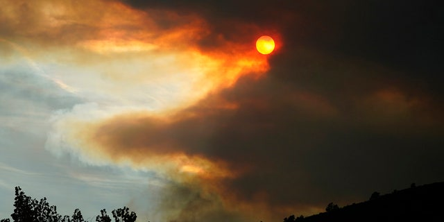 Smoke obscures the sun as fire approaches a ridge along Highway 36 as several wildfires burn in the state Wednesday, Oct. 21, 2020, south of Lyons, Colo.