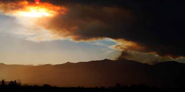 The smoke plume obscures the sun as smoke tops a ridge in this view from 75th Street as several wildfires burn in the state Wednesday, Oct. 21, 2020, in Niwot, Colo.