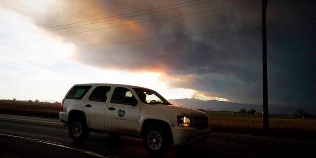 Smoke rises from mountain ridges as several wildfires burn in the state Wednesday, Oct. 21, 2020, as traffic moves along 75th street in Niwot, Colo.