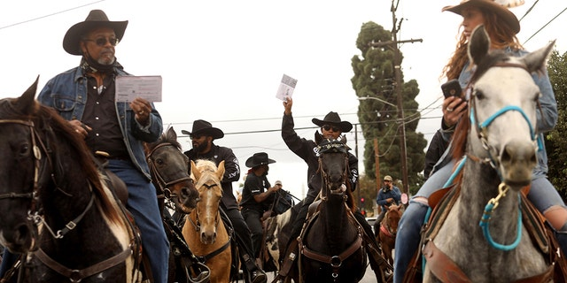Compton Cowboys, some lifting their ballots, ride through the streets of Compton toward the Compton Library to cast their votes in a ballot box on October 25, 2020. (Photo by Genaro Molina/Los Angeles Times via Getty Images)