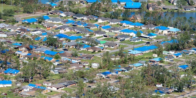 Blue tarps cover houses in the aftermath of Hurricane Delta, Saturday, Oct. 10, 2020, in Iowa, La.