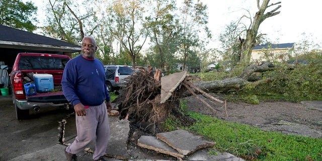 Marcus Peterson walks past a downed tree in his yard after Hurricane Delta moved through, Saturday, Oct. 10, 2020, in Jennings, La.