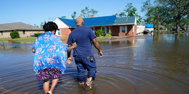 Soncia King holds onto her husband Patrick King in Lake Charles, La., Saturday, Oct. 10, 2020, as they walk through the flooded street to their home, after Hurricane Delta moved through on Friday.
