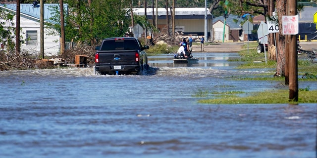 A truck drives through floodwaters in a neighborhood in Lake Charles, La., Saturday, Oct. 10, 2020, after Hurricane Delta moved through on Friday.