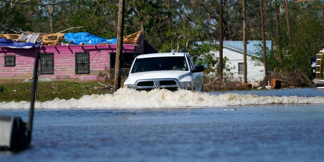 A truck drives through a flooded street in Lake Charles, La., Saturday, Oct. 10, 2020, past a home with damage from Hurricane Laura, after Hurricane Delta moved through on Friday.