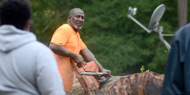 Carey Blackmon cuts an oak tree after it fell on the home of Larry Veal, Saturday, Oct. 10, 2020, in Gloster, Miss., during Hurricane Delta.