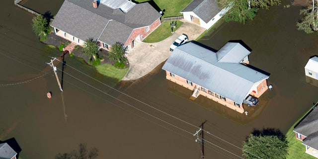Houses surrounded by flood waters are seen in the aftermath of Hurricane Delta Saturday Oct. 10, 2020, in Welsh, La.