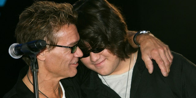 Eddie Van Halen (L) and son Wolfgang hug at the Van Halen press conference announcing their new tour at the Four Seasons Hotel on August 13, 2007, in Los Angeles, California.