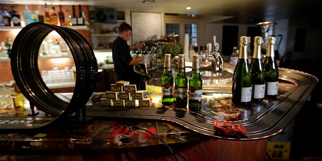 A bartender prepares a drink after turning a bar area into an electric car track. (REUTERS/David W Cerny)
