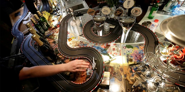 A bartender plays with an electric car track inside a cafe bar, as the Czech government shut all restaurants for two weeks to slow down the spread of COVID-19, in Prague, Czech Republic. (REUTERS/David W Cerny)