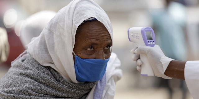 Officials take Lideta Church visitors' temperature as a precaution against the novel coronavirus (Covid-19) pandemic in Addis Ababa, Ethiopia on June 9. (Photo by Minasse Wondimu Hailu/Anadolu Agency via Getty Images)