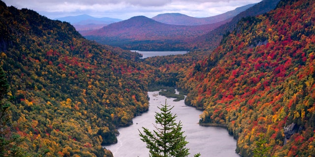 Hardwood trees show their fall colors on mountainsides flanking Lower Ausable Lake in the Adirondacks, Sunday, Sept. 27, 2020, near Keene Valley, N.Y.
