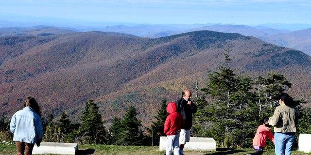 Visitors to the summit of Mount Equinox in Manchester, Vt., look at foliage to the north Monday, Oct. 12, 2020, as many motorists traveled to the peak to view the autumn colors on the Columbus Day holiday weekend.