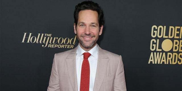 Paul Rudd passes out cookies to voters waiting in the rain