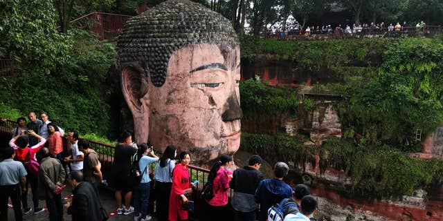 Tourists visit the Leshan Giant Buddha, a UNESCO World Heritage Site, on the first day of the eight-day National Day holiday on October 1. (Liu Zhongjun/China News Service via Getty Images)