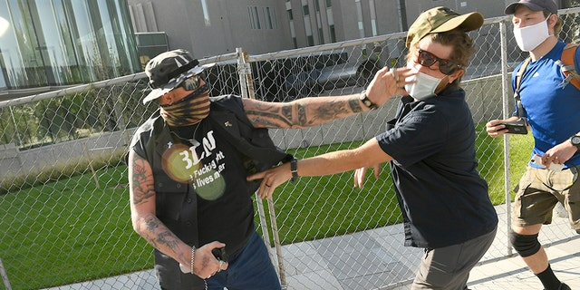 "A man punches another man after a Saturday rally in Denver. The man on the left side of the photo was supporting the ""Patriot Rally"". He engaged with the man on the right, hit him in the face and sprayed him with mace. The man on the right, then shot and killed the protester at left. The man who was killed, identified as Lee Keltner, operated a hat-making business in the Denver area. (Photo by Helen H. Richardson/MediaNews Group/The Denver Post via Getty Images)"