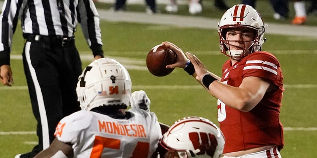 Wisconsin quarterback Graham Mertz throws a pass during the first half of an NCAA college football game against Illinois Friday, Ott. 23, 2020, in Madison, Wis. (AP Photo/Morry Gash)