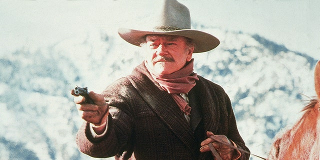 American actor John Wayne (1907 - 1979) aims a gun while riding horseback in a scene from 'The Shootist,' 1976. 'The Shootist,' the story of a dying gunfighter living out his last days, was Wayne's last film.