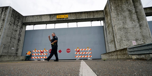 A Plaquemines Parish sheriff deputy walks away after workers closed a floodwall gate on Hwy 39 in Poydras, La., Wednesday, Oct. 28, 2020.