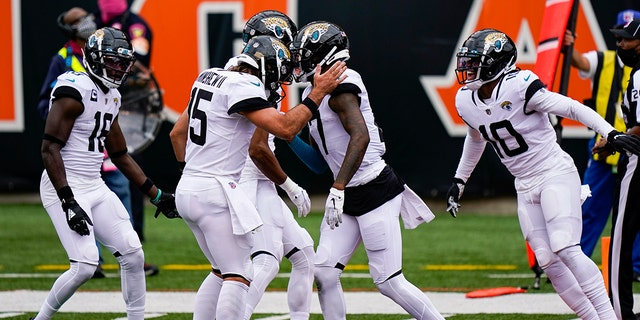 Jacksonville Jaguars wide receiver D.J. Chark (17) right celebrates a touchdown catch with quarterback Gardner Minshew (15) in the first half of an NFL football game against the Cincinnati Bengals in Cincinnati, Sunday, Oct. 4, 2020. (AP Photo/Bryan Woolston)