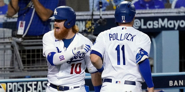 Los Angeles Dodgers' Justin Turner, left, and A.J. Pollock (11) celebrate after Pollock scored on a double by Mookie Betts during the fifth inning in Game 2 of the team's National League wild-card baseball series Thursday, Oct. 1, 2020, in Los Angeles. (AP Photo/Ashley Landis)